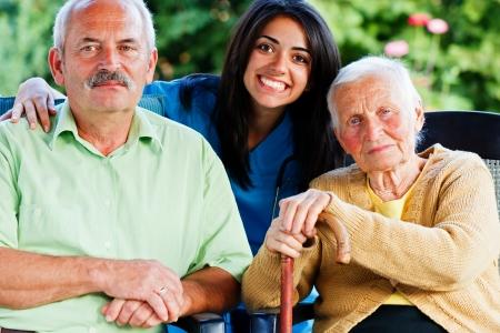 Feliz grupo de personas - médico, cuidador, enfermera con dos pacientes en el jardín de la residencia de ancianos.