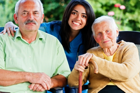 carer: Happy group of people - doctor, carer, nurse with two patients in the garden of the nursing home. Stock Photo