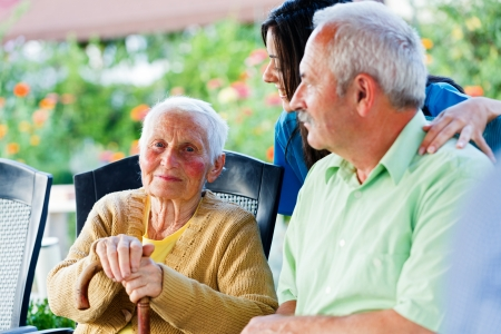 elderly care: Happy elderly patient with doctor and visitor. Stock Photo