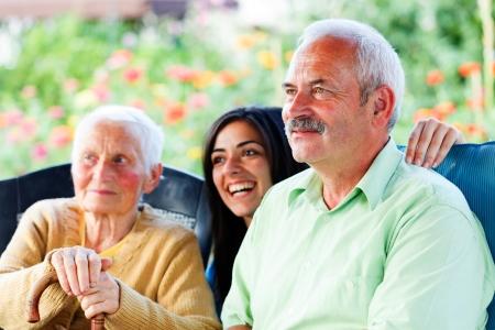 Glimlachende oude man op bezoek bij haar bejaarde moeder in het verpleeghuis. Stockfoto