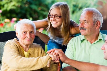 Bejaarde vrouw verwelkomen haar familie - zoon en kleindochter in de tuin van het verpleeghuis.