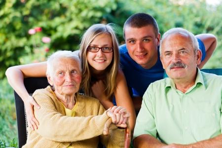 personas ayudando: Familia feliz que visitar a la abuela en el jard�n de la residencia de ancianos.