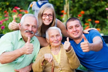 Gelukkig, tevreden familie thumbsup voor de kwaliteit van de residentiële zorg van oma.