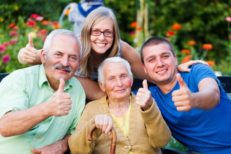 contented: Happy, contented family showing thumbsup for the quality of the residential care of grandmother. Stock Photo