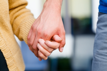 Young caring hand holding an elderly womans weak hand. Stock Photo
