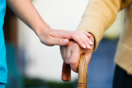 home care nurse: Doctor holding a senior patiens s hand on a walking stick - special medical care concept for Alzheimer s syndrome. Stock Photo