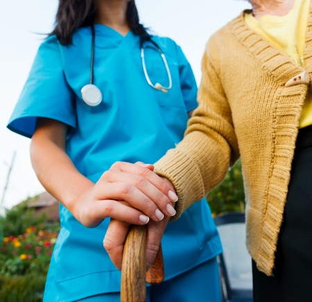 nursing aid: Doctor holding a senior patiens s hand on a walking stick - special medical care concept for Alzheimer s syndrome. Stock Photo
