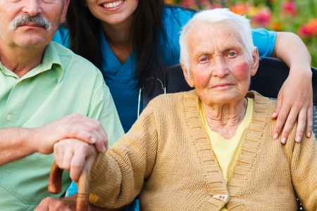 patients: Elderly woman surrounded by family and doctor. Stock Photo