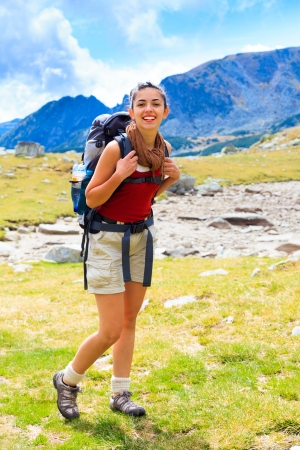 Woman with backpack being happy while hiking. photo
