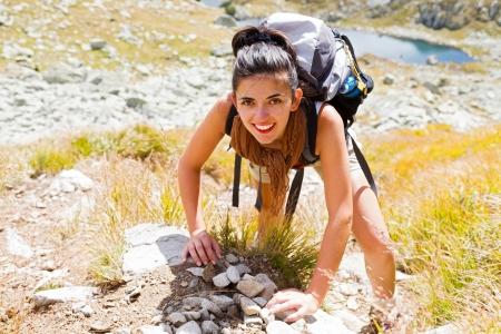 Woman enjoying climbing up a rocky mountain with big backpack. photo