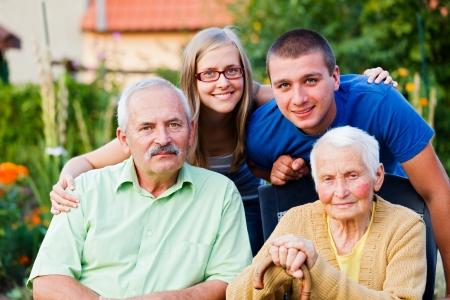 ni�os ayudando: Feliz familia multigeneracional visitar el miembro m�s viejo - la abuela - en un hogar de ancianos. Foto de archivo