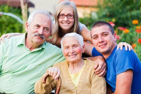 Generaties in een beeld: grootmoeder, zoon en jonge kleinkinderen in de tuin van het verpleeghuis. Stockfoto