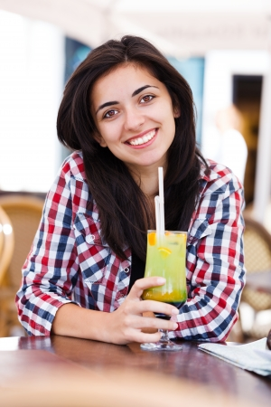 Beautiful young woman smiling to the camera, drinking cocktail in a restaurant. photo