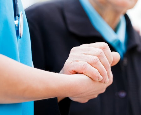 needy: Caring nurse or doctor holding elderly ladys hand with care. Stock Photo
