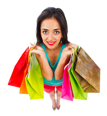 kindly: Attractive woman with shopping bags smiling kindly - white background.