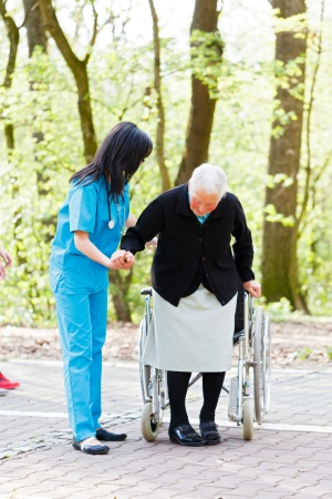 Caring nurse or doctor helping senior patient to sit down on her wheelchair.