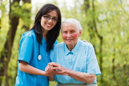 Soort verpleegster samen met bejaarde in de tuin van het ziekenhuis.