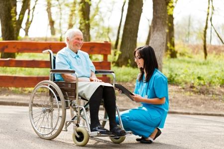 Nurse or doctor writing on chart near elderly patient in wheelchair. Archivio Fotografico