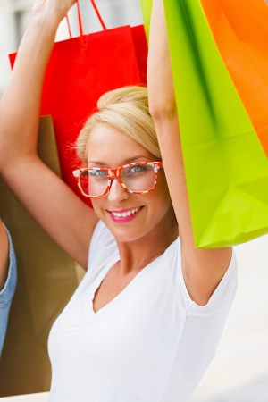 kindly: Beautiful blond girl with shopping bags raised in the air smiling kindly.