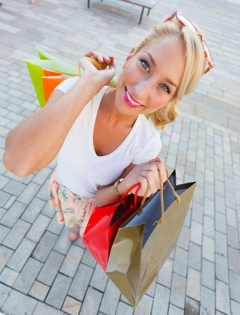 Gorgeous young woman smiling with shopping bags - wide angle. Stock Photo - 23343021