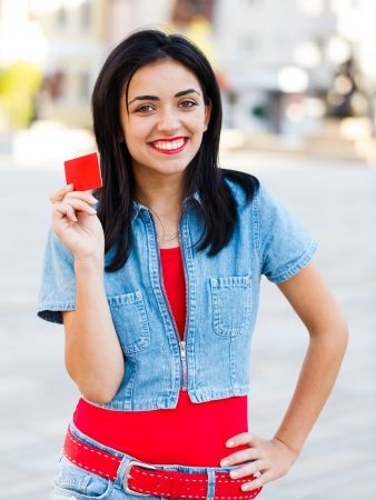 Smiling brunette woman holding a red empty credit card in the city center. Stock Photo - 23343038