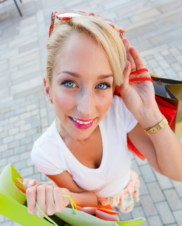 Beautiful young blond girl out shopping in the city. Stock Photo - 23343042