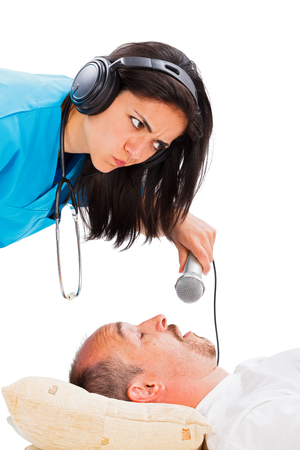 snoring: Funny image of a doctor listening to a mans snoring through her headset.
