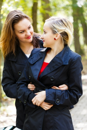 glancing: Beautiful fraternal twin sisters glancing at each other while hugging and loving.