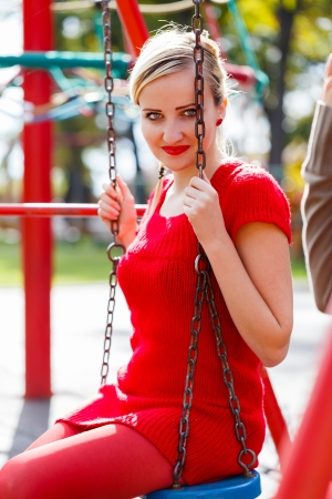 Young woman sitting on swing reviving childhood. Stock Photo - 23343467