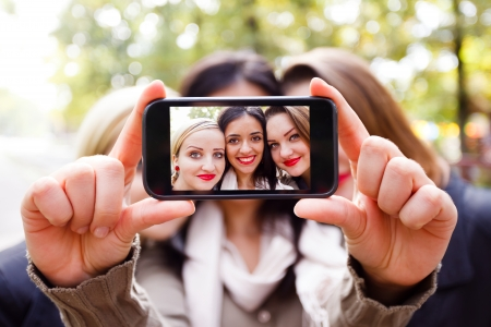 selfie: Students taking a self portrait with smart phone.