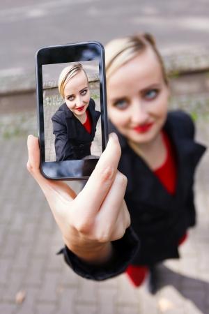 Blond meisje die een selfshot met smartphone.