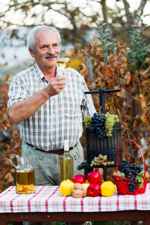 contended: Senior man cheering with a glass of wine, contended by this years crop produce. Stock Photo