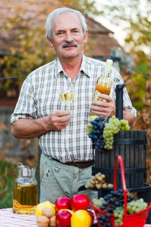 oenology: Happy elderly man with wine and harvest crops. Stock Photo