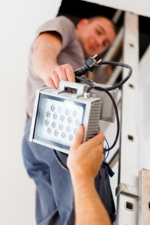 Electrician team handing light making good workflow. Stock Photo