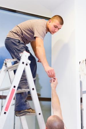 Elektriker auf Leiter geben oder sich etwas von seinem Teamkollegen. Standard-Bild - 23226011