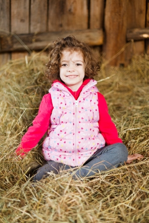 Smiley little beauty sitting in hay having fun. photo