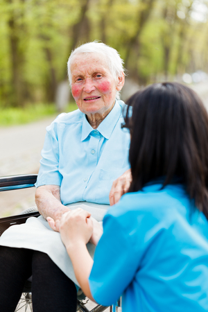 Sitting elderly ladys hand held by nurse. photo