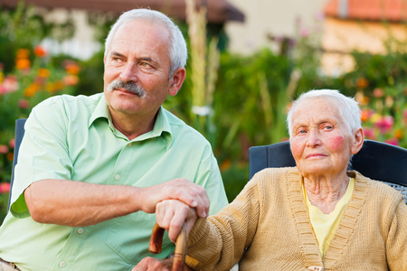 alzheimers: Elderly woman with her son in the residential home. Stock Photo