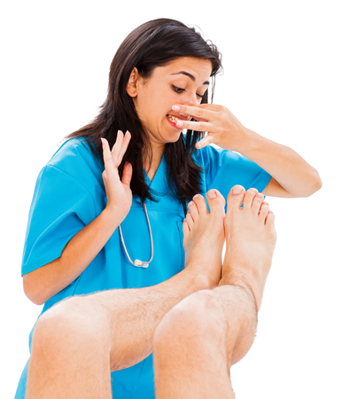stinky: Doctor defending herself from stinky man feet - isolated on white. Stock Photo