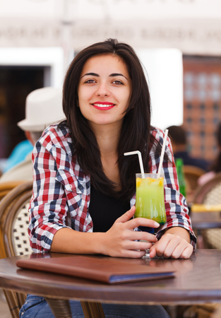 Beautiful latina girl drinking juice with straw in a restaurant. photo