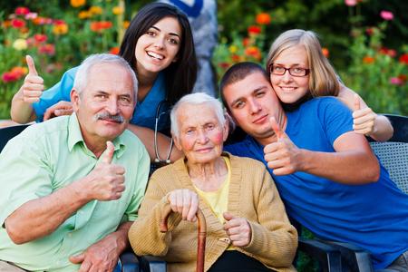 Gelukkig groep mensen - familie en arts - thumbsup voor de hoge kwaliteit van de dienstverlening in het verzorgingshuis.