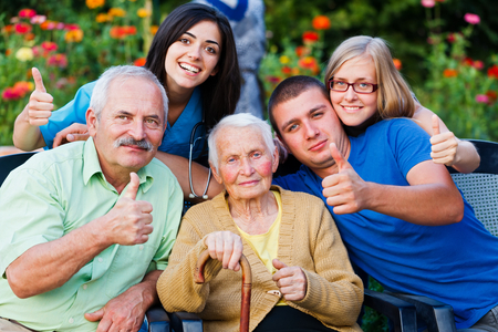 homecare: Happy group of people - family and doctor - showing thumbsup for the high quality services in the residential home.