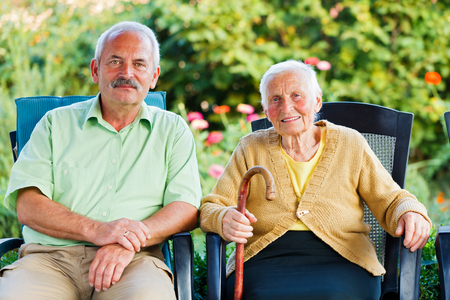 Happy elderly woman in a nursing home with her visitor - her son. Stock Photo
