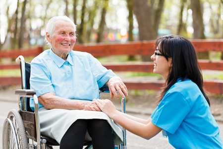 Kind nurse holding elderly ladys hand while chatting with her. photo