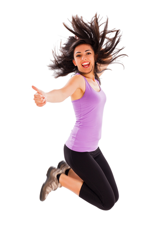 Pretty fit girl showing like sign while jumping high - studio shot. Stock Photo