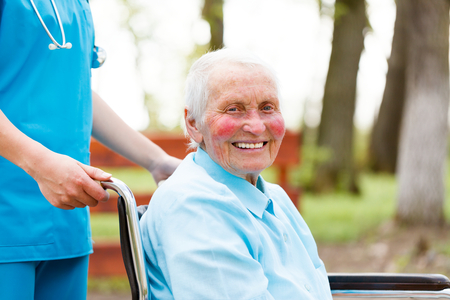 cancer patient: Smiling senior woman outdoors in wheelchair walked by nurse.