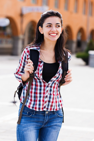 kindly: Kindly smiling woman or student on street with backpack.