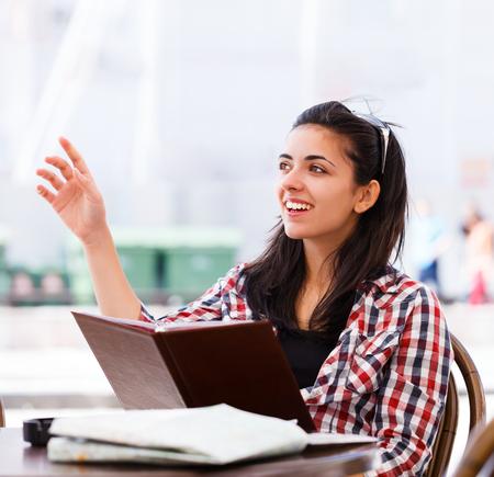 ordenanza: Mujer joven feliz con el restaurante 's menú en la mano llamando al camarero o la camarera de la ordenanza. Foto de archivo