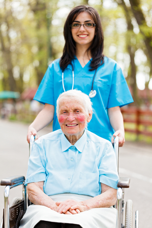 Nice nurse walking with elderly lady in wheelchair. photo
