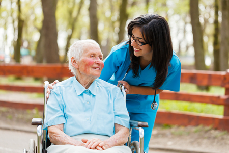 Nurse and elderly lady in wheelchair chatting outdoors.